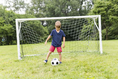 Young Boy with football on a field having fun Royalty Free Stock Image