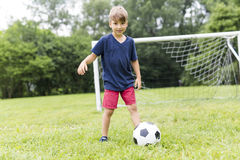 Young Boy with football on a field having fun Royalty Free Stock Photography