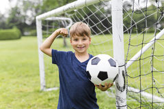Young Boy with football on a field having fun Stock Image