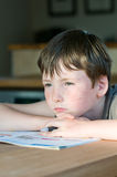 Young boy with freckle. At homework or school thinking Stock Images