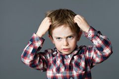 Young boy with freckles scratching his hair for head lice. Annoyed young boy with freckles scratching his hair for head lice or allergies, grey background studio Royalty Free Stock Image