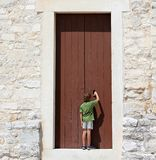Young boy in front of a big door. Young boy standing in front of a big door royalty free stock images