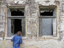 Young boy in front of an old window. A curious young boy peeping in a window of a ruined old house stock photo