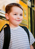 Young boy in front of yellow school bus Stock Photos