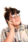 A young boy in funny glasses. Smiling and talking on the phone Stock Images
