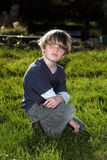 Young boy in garden looking over his shoulder. A young blonde haired boy sits in a sunny garden and is lost in thought Stock Photography