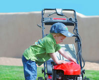 Young boy and garden mower. A little boy playing with a garden mower Stock Photography