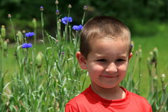 Young boy in garden,smiling at his mom stock photography