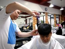 A young boy gets a haircut at a barber shop. Royalty Free Stock Photography
