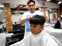 A young boy gets a haircut at a barber shop. Stock Images
