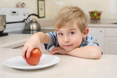 Young boy getting an apple for a snack stock image