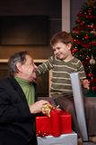Young boy getting christmas present from grandfather Royalty Free Stock Photos