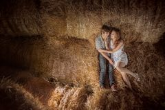 Young boy and gil lyingYoung boy and gyrl lying in hay.  Outdoor summer portrait of beautiful couple. in hay. Outdoor summer portr Stock Image