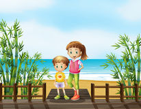 A young boy and a girl at the bridge near the beach Stock Photos