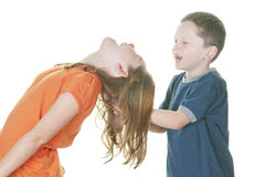 Young boy and girl fighting. Young boy and girl being physical Royalty Free Stock Image