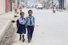 Young boy and girl going home from school after lessons at the local school in Kathmandu, Nepal Royalty Free Stock Images