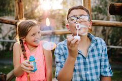 Young boy and girl having fun blowing soap bubbles stock photography