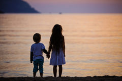 Young boy and girl holding hands while standing on beach Royalty Free Stock Images
