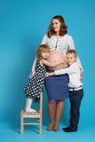 Young boy and girl hug pregnant mother Stock Photos