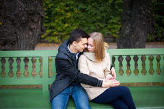 Young boy and girl hugging and kissing, sitting on the bench.  Royalty Free Stock Photography