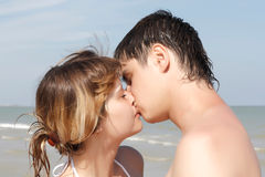 A young boy and girl kissing on the beach Stock Photos