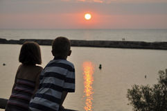 Young boy and girl overlooking sunset and water Royalty Free Stock Images