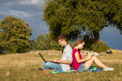 Young boy and girl in park with laptop and book. Stock Images