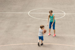 Young boy and girl playing basketball Stock Photo