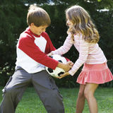 Young boy and girl playing with a football in a garden Royalty Free Stock Photos