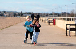 Young boy and girl playing on scooters. Young brother and sister speeding along a beach promenade on new silver scooters Royalty Free Stock Photo