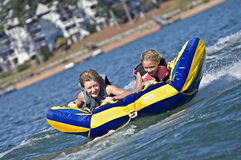 Young Boy and Girl Riding a Tube on Water. Young boy and girl on a tube behind a boat royalty free stock images
