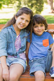 Young boy and girl sitting on park bench Stock Photography
