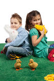 Young boy and girl sitting together. Easter theme with a young boy and girl sitting together holding a toy bunny and a toy chick while looking at the camera Stock Photos