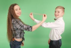Young boy and girl stretching from chewing gum which he carries in his mouth Royalty Free Stock Photography