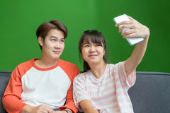 Young boy and girl teenager using mobile phone to selfie themsel. Ves at sofa in home Royalty Free Stock Photos