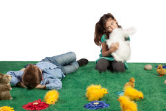 Young boy and girl with toy bunnies and chicks. Easter theme with young boy lying down and girl cuddling her toy bunny Royalty Free Stock Image