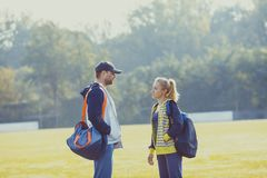 Boy and girl talking before workout. Young boy and girl before training talking in the stadium, preparing for workout Royalty Free Stock Image