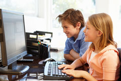 Young boy and girl using computer at home Royalty Free Stock Photography