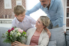 Young boy giving flowers to his mother. Young boy giving flowers to mommy for mother's day Royalty Free Stock Photography
