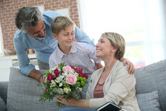 Young boy giving flowers to his mother. Young boy giving flowers to mommy for mother's day Royalty Free Stock Images