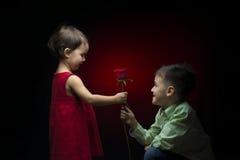 Young boy giving a rose to a little girl Stock Photos