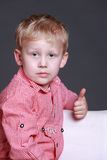 Young boy giving a thumbs up gesture. Young blonde boy sitting looking at the camera giving a thumbs up gesture of approval and success Stock Photo