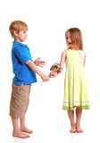 Young boy giving young girl flowers Royalty Free Stock Photography