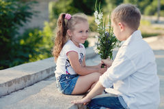 A young boy is givving flowers to the girfriend on a date Royalty Free Stock Photo