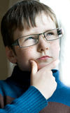Young boy with glasses. Serious young boy portrait with glasses near the window Royalty Free Stock Images