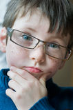 Young boy with glasses. Young boy portrait with glasses seems surprised Royalty Free Stock Image