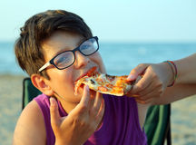 Young boy with glasses eats a slice of pizza Royalty Free Stock Photography