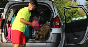 Young boy with glasses loaded the luggage in the trunk. Of the car before the trip Stock Image