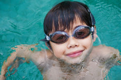 Young boy with goggles swimming in pool Stock Photography