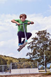 Young boy going airborne with his scooter. At the skate park royalty free stock image